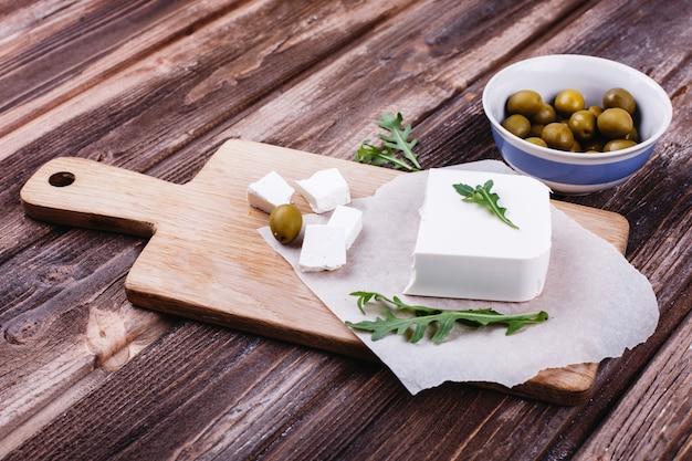 Comida fresca e saudável. delicioso jantar italiano. queijo fresco servido na tábua de madeira Foto gratuita