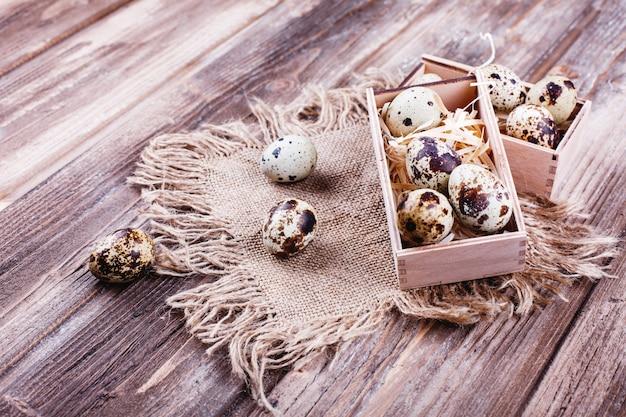 Comida fresca e saudável, proteína. ovos de codorna em caixa de madeira fica sobre a mesa rústica Foto gratuita