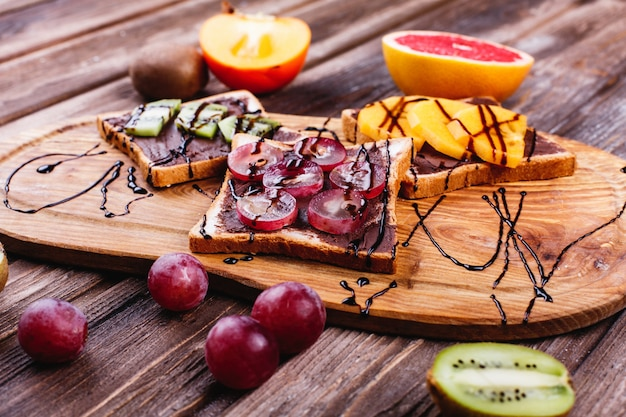 Comida fresca, saborosa e saudável. idéias de almoço ou café da manhã. pão com manteiga de chocolate, uva Foto gratuita