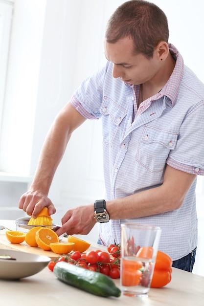 Comida. homem lindo na cozinha Foto gratuita