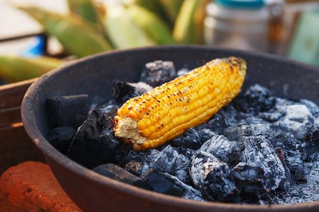 Comida indiana na praia - espigas de milho fresco são assadas sobre as brasas. Foto Premium