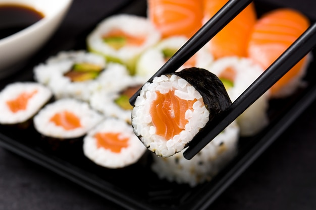 Comida japonesa: sushi maki e nigiri conjunto em preto, close-up Foto Premium