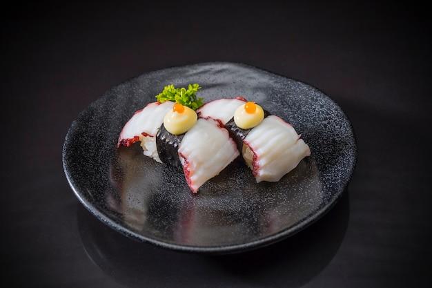 Comida japonesa, tako nigiri sushi servido em prato de cerâmico, sushi nigiri em fundo preto Foto Premium