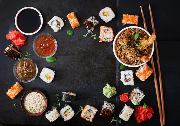 Comida japonesa tradicional - sushi, pãezinhos, arroz com camarão e molho em um fundo escuro. vista do topo Foto gratuita