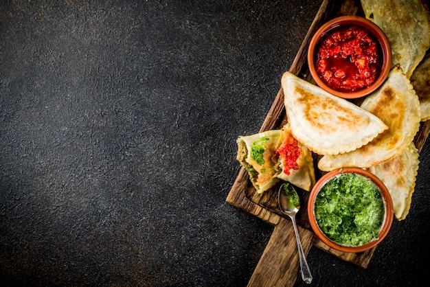 Comida latino-americana, mexicana e chilena. empanadas de massa assada tradicional com carne de bovino, dois molhos picantes Foto Premium