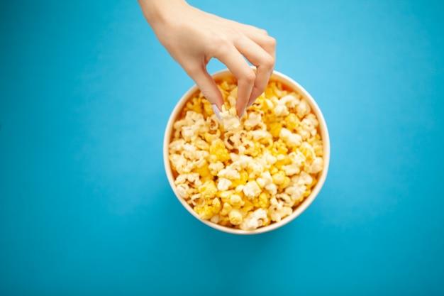 Comida. mão de mulher que leva pipoca do balde. balde de pipoca. cinema Foto Premium