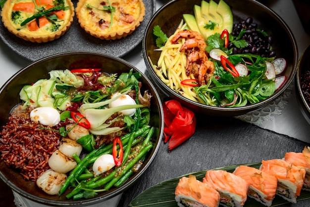 Comida mista, há pratos diferentes na mesa do restaurante, para pessoas diferentes Foto Premium