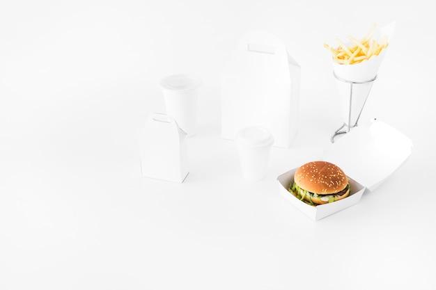 Comida rápida; copa de eliminação e parcela de alimentos simulado acima no pano de fundo branco Foto gratuita