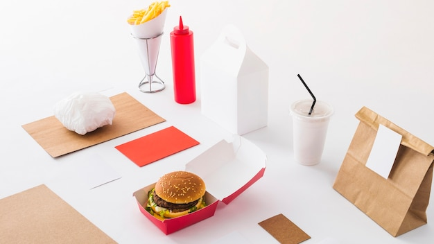 Comida rápida; copo de eliminação; garrafa de molho e parcela em fundo branco Foto gratuita