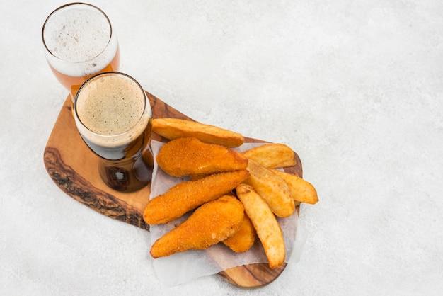 Comida saborosa e copos de cerveja de alto ângulo Foto gratuita