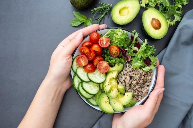 Comida saudável. a mão da mulher segurando a tigela de budha com quinoa, abacate, pepino, salada, tomate, azeite de oliva. Foto Premium
