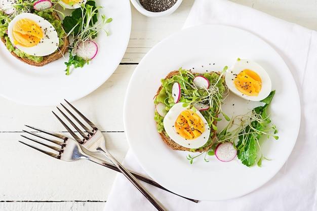 Comida saudável. café da manhã. sanduíche do ovo do abacate com pão inteiro da grão no fundo de madeira branco. vista do topo. lay plana Foto Premium