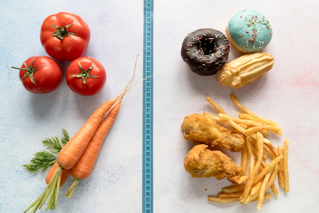 Comida saudável e alimentos pouco saudáveis divididos de fita de medição Foto gratuita