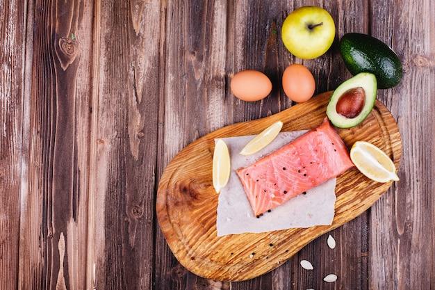 Comida saudável e fresca. salmão cru servido com limões, ovos, maçãs, abacate e facas Foto gratuita