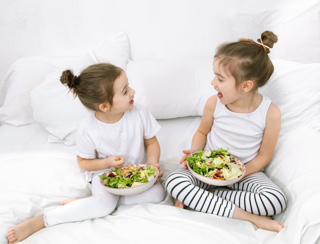 Comida saudável em casa. felizes dois filhos bonitos comendo frutas e legumes no quarto na cama. alimentação saudável para crianças e adolescentes. Foto gratuita
