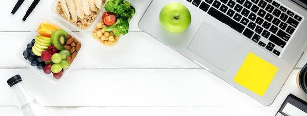 Comida saudável na caixa de refeição definido na mesa de trabalho com laptop Foto Premium