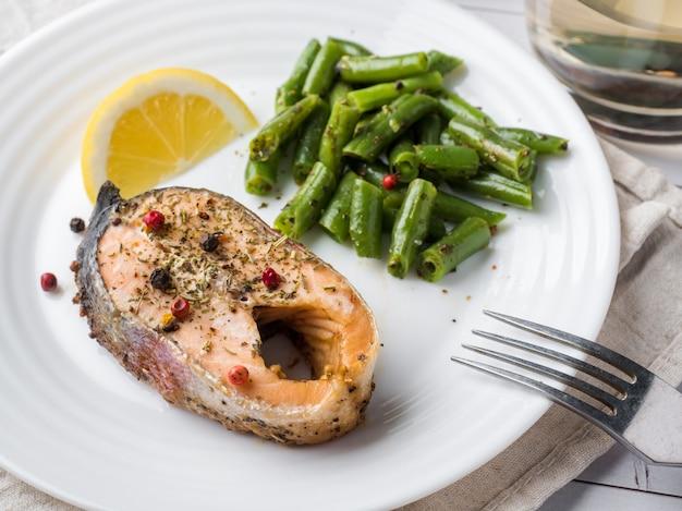 Comida saudável. peixe vermelho assado, salmão rosa, salmão e feijão verde com uma fatia de limão em um prato Foto Premium