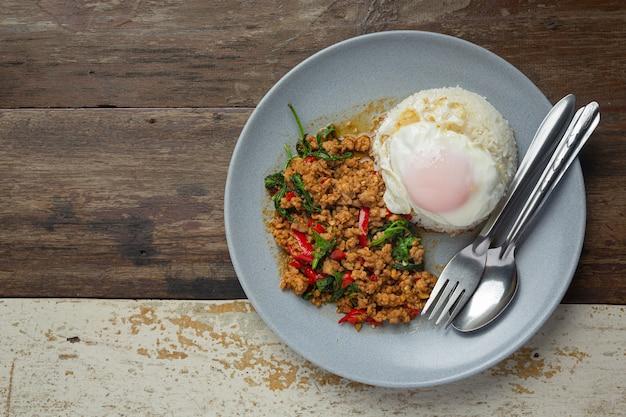 Comida tailandesa; carne de porco picada com manjericão com arroz e ovo frito Foto gratuita