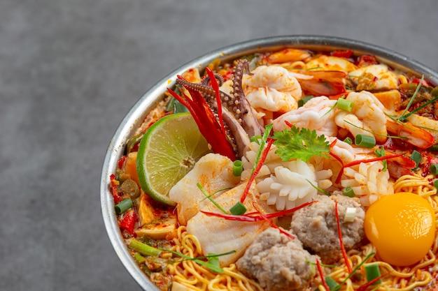 Comida tailandesa. macarrão picante ferva com frutos do mar e carne de porco na panela quente Foto gratuita