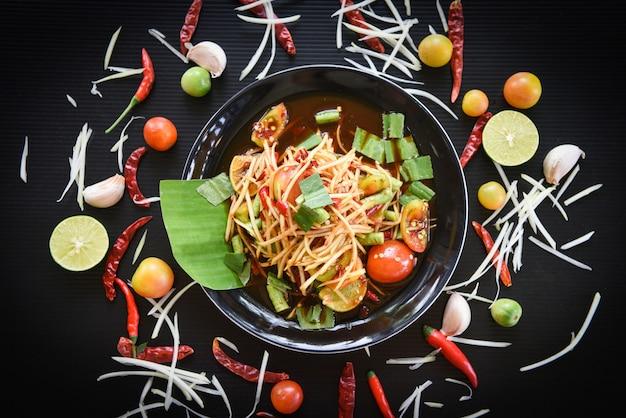 Comida tailandesa picante de salada de papaia verde em cima da mesa Foto Premium