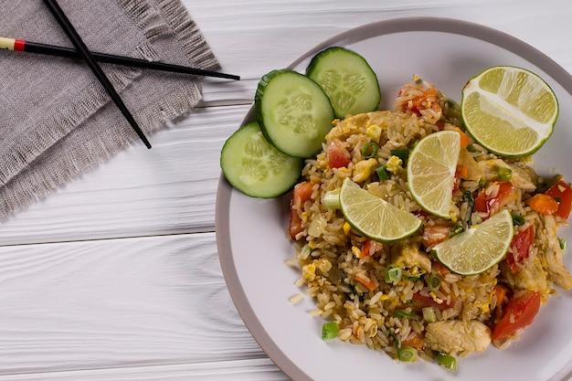 Comida tradicional tailandesa. arroz frito com legumes, especiarias e limão. khao pad Foto Premium