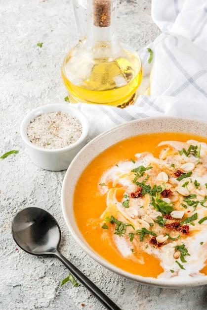 Comida vegan moderna, sopa de desintoxicação de batata doce com leite de coco, tomate seco, amendoim e ervas Foto Premium