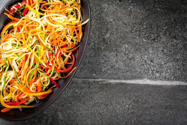 Comida vegetariana, dieta. macarrão de legumes, macarrão com cenoura, abobrinha, pimentão. pronto para assar cozinhar sobre uma mesa de pedra. vista superior copyspace Foto Premium