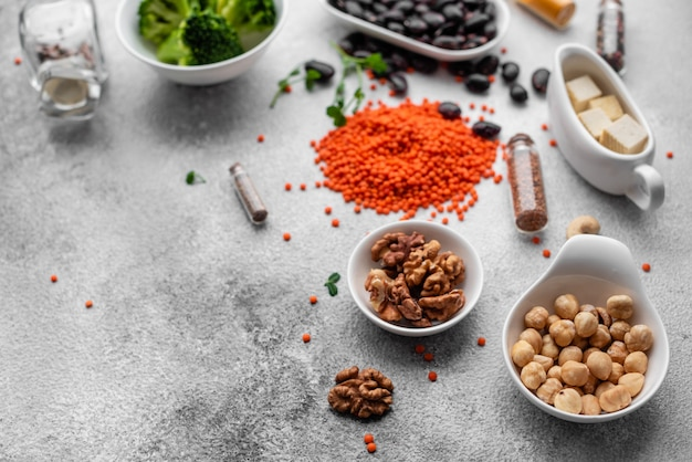 Comida vegetariana saudável em um fundo de concreto com espaço de cópia. nozes, feijões, verduras e sementes Foto Premium