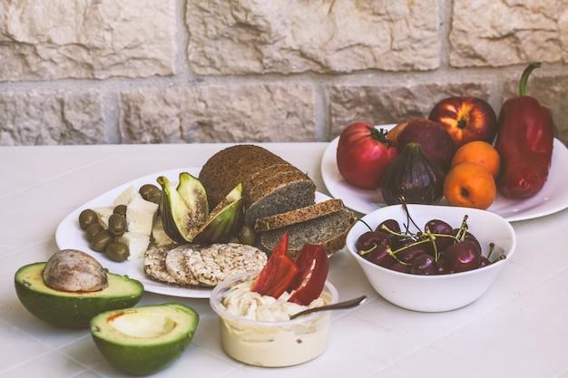 Comida vegetariana saudável europeu em uma mesa branca na varanda Foto Premium
