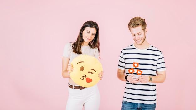 Como ícones sobre o homem usando o telefone celular, além de mulher segurando beijo emoji Foto gratuita