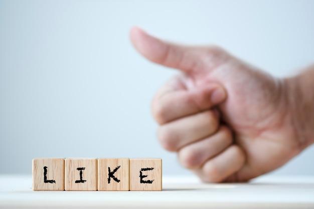 Como palavra-chave em madeira cúbica e punho mostrando o polegar para cima gesto Foto Premium