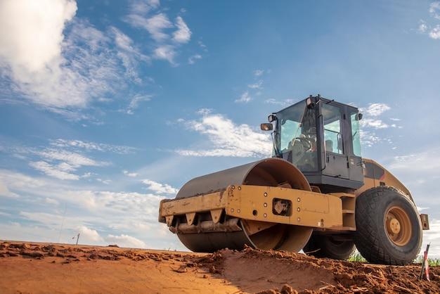 Compactador amarelo no local de construção de estradas Foto Premium