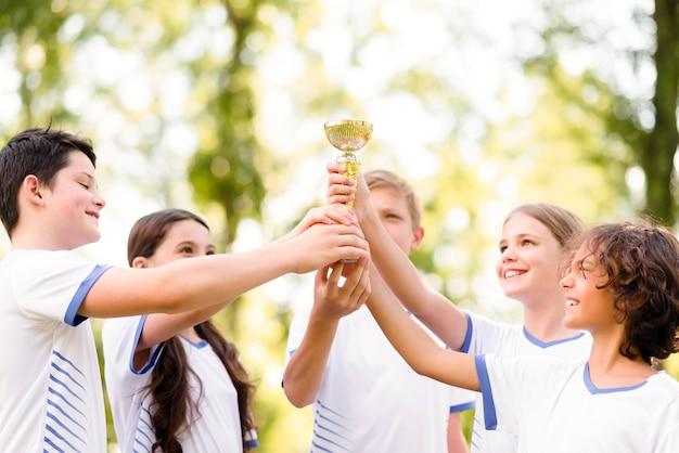Companheiros de equipe segurando um troféu de ouro Foto gratuita
