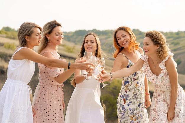 Companhia de amigas desfruta de um piquenique de verão e levanta copos com vinho Foto Premium
