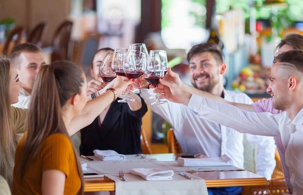Companhia de amigos comemora reunião em um restaurante. Foto Premium