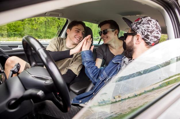 Companhia de amigos felizes cumprimentando uns aos outros no carro Foto gratuita