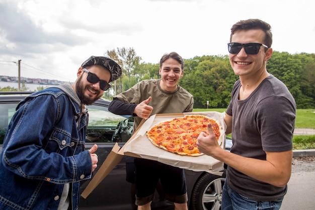 Companhia de jovens com pizza fazendo excelente sinal na natureza Foto gratuita