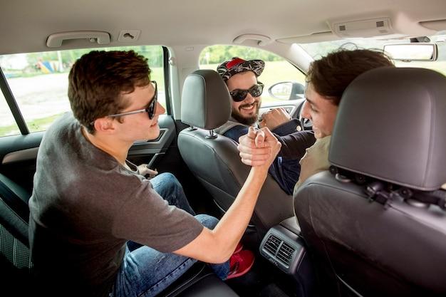 Companhia de jovens rapazes acolhendo um ao outro no carro Foto gratuita