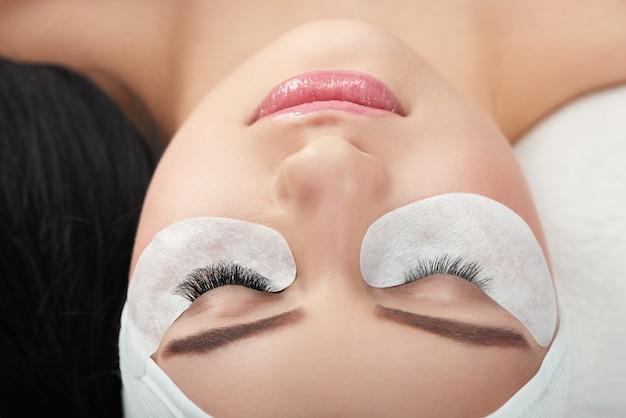Comparação de fotos dos cílios normais e aumentados da mulher. Foto Premium