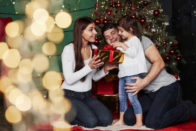 Compartilhando férias com a filha. linda família senta-se perto da árvore de natal com caixas de presente na noite de inverno, aproveitando o tempo que passam juntos Foto Premium