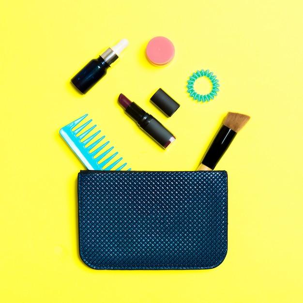 Compõem produtos derramando fora da bolsa de cosméticos em amarelo Foto Premium