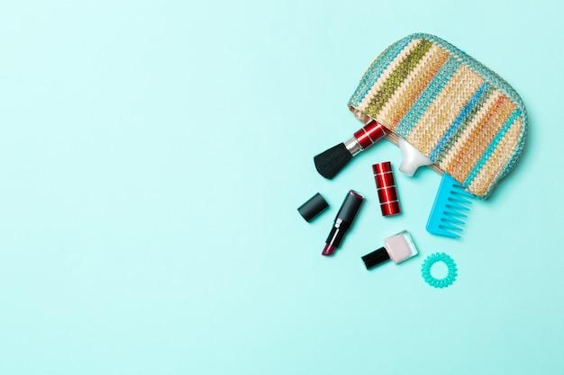 Compõem produtos derramando fora da bolsa de cosméticos, sobre fundo azul pastel Foto Premium