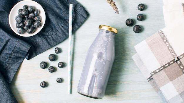 Composição azul com smoothie de mirtilo Foto gratuita