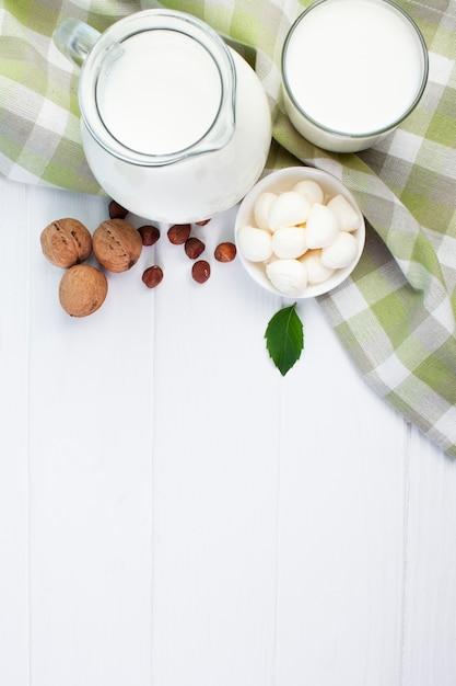 Composição branca de leite com fundo de madeira Foto gratuita
