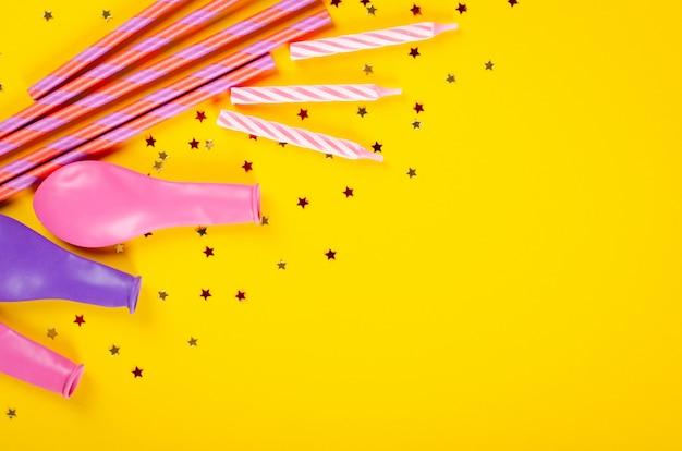 Composição colorida das palhas bebendo e dos balões de ar na decoração amarela do fundo, do partido e da celebração. Foto Premium