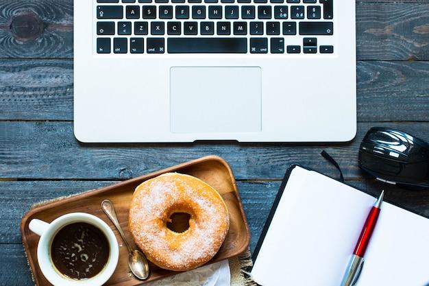 Composição colorida do café da manhã dos anéis de espuma com portátil e caneca de café Foto Premium