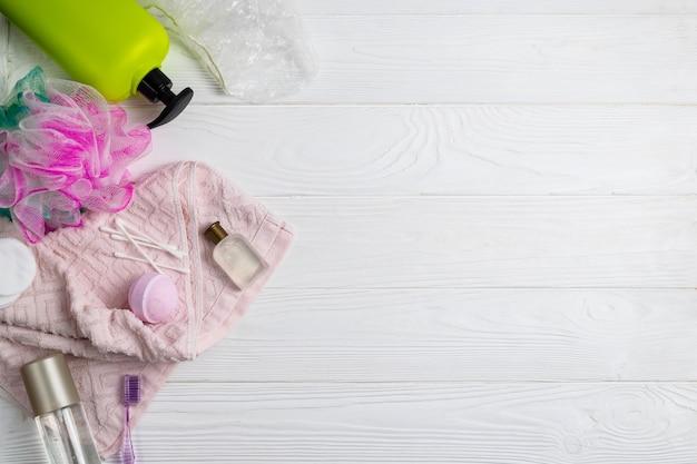 Composição, com, banho, acessórios, chuveiro, gel, toalha toalha washcloth, escova de dentes, branco, fundo madeira, com, copyspace Foto Premium