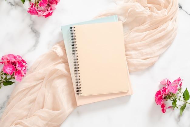 Composição com caderno de papel em branco, flores cor de rosa e cobertor pastel Foto Premium