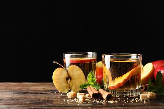 Composição com cidra, açúcar, canela e maçãs na mesa de madeira Foto Premium
