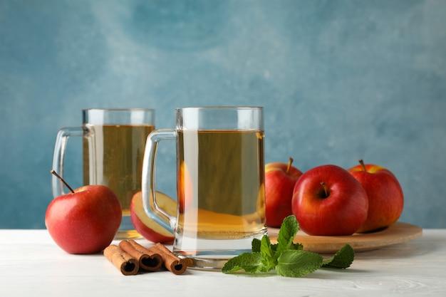 Composição com cidra, canela e maçãs na mesa de madeira branca Foto Premium